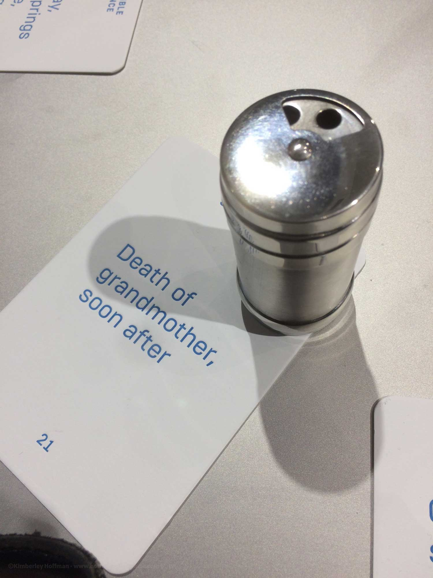 "Photo of a small stainless steel spice jar and a card labelled ""Death of grandmother soon after"""