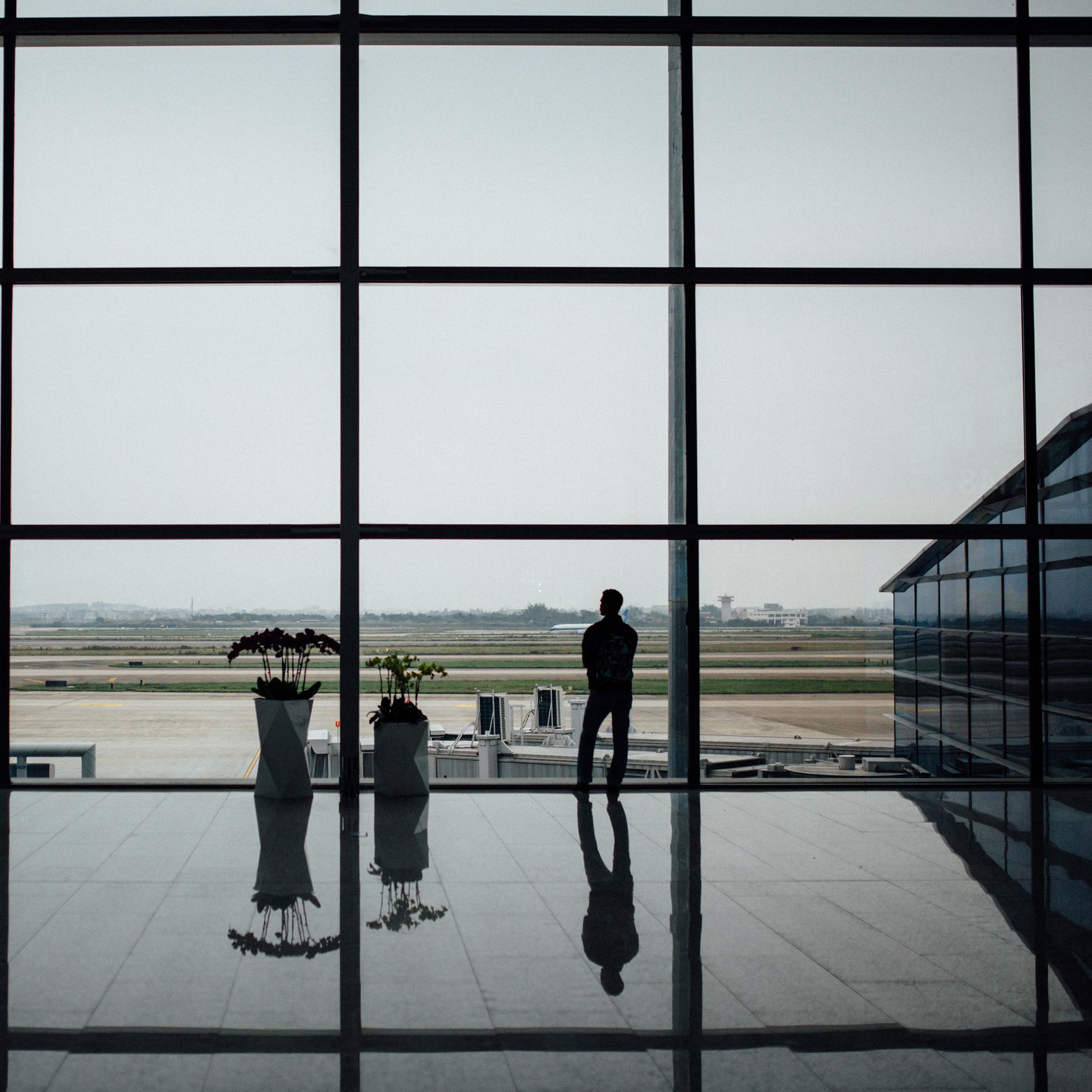 Foto von Hanson lu am Unsplash Das Beste zum Schluss: Foto eines Menschens, der am Flughafen einsam und allein auf etwas wartet. Er schaut durch die große Fensterscheiben auf die Landebahn.